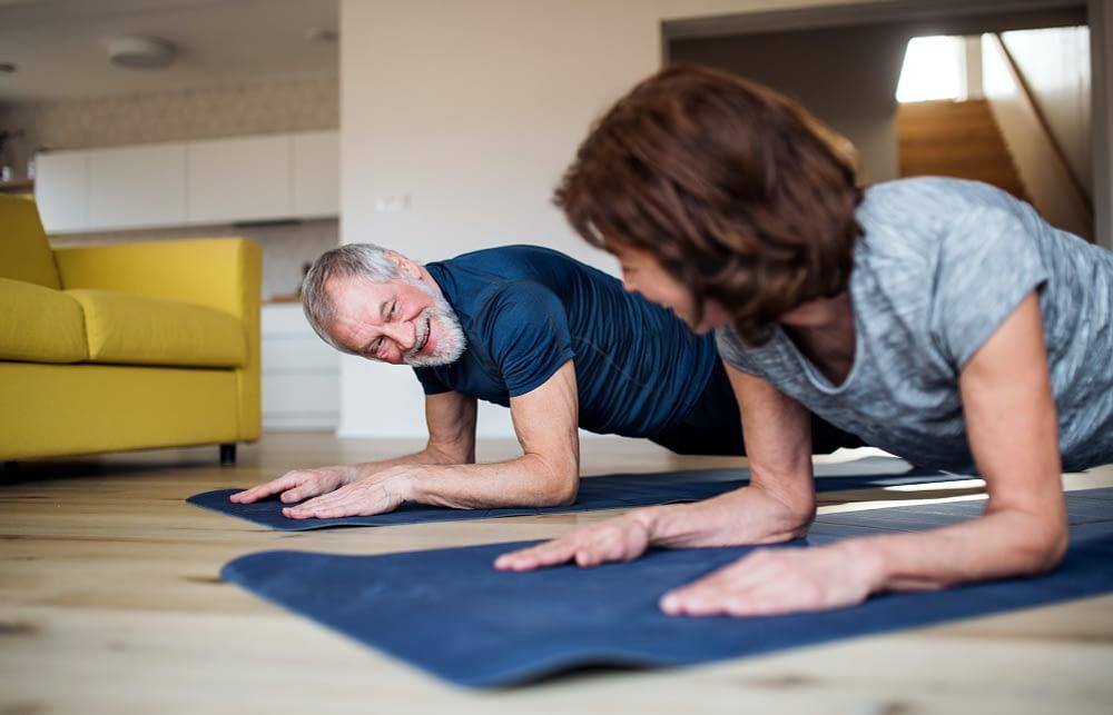 older client couple doing planks