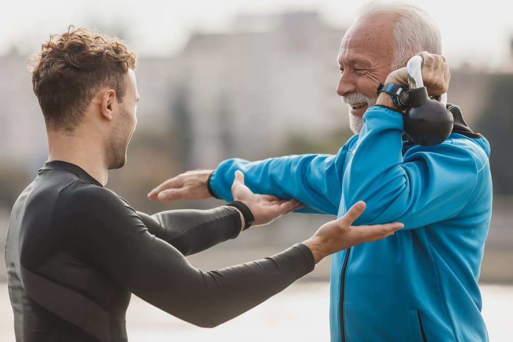Older male client with personal trainer